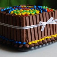 Peaunut butter candy cake decorates with KitKats, M&M's, and Hershey's Kisses.